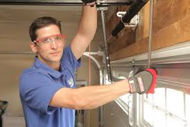 A garage door repair Minnesota specialist repairs a door
